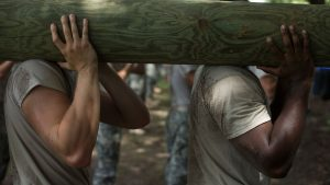 Two men carry a log over their shoulder
