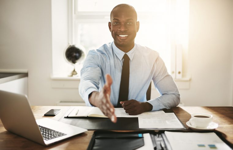 smiling young executive sitting at his desk preparing for job interviews
