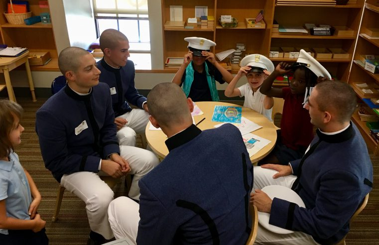 Freshmen cadets teach James Simons elementary school children about heroes and help them make cards