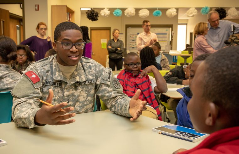 A Citadel cadet sits with a young student at Simmons Pickney Middle School during an after school program sponsored by the Patricia McArver Public Speaking Lab.