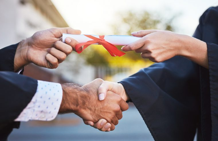 instructor handing a man his diploma while shaking his other hand