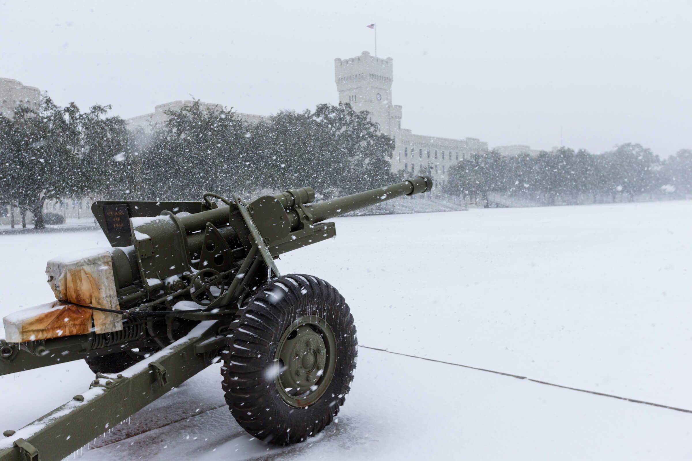 Snow accumulates on Summerall Field with a cannon in the foreground