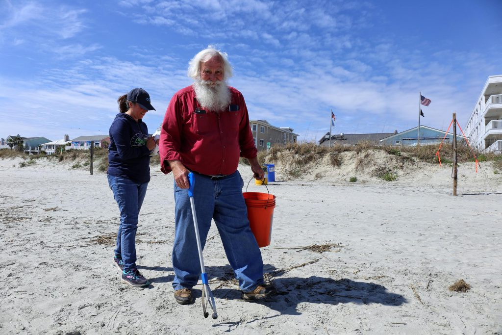 Howard Hogue, known as Beach Santa, and Linda Rowe pick up litter on the Isle of Palms (Courtesy: Victoria Hansen, SC Public Radio)