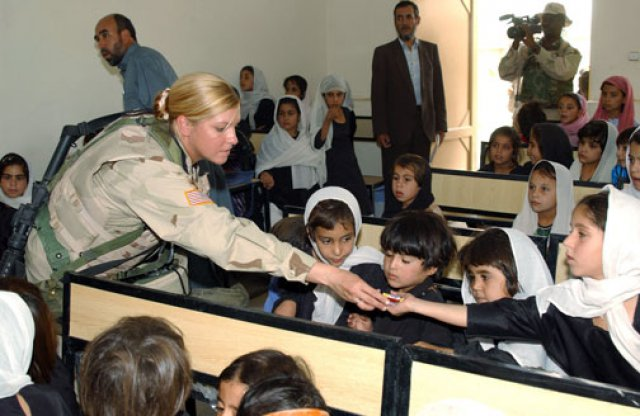 Staff Sgt. Jen Brooks, with the Kandahar Provincial Reconstruction Team, gives candy to students from the Abdul Karzai Middle School in Khandahar, Afghanistan, Sept. 14, 2004. (Photo Credit: Staff Sgt. Joseph P. Collins Jr.)