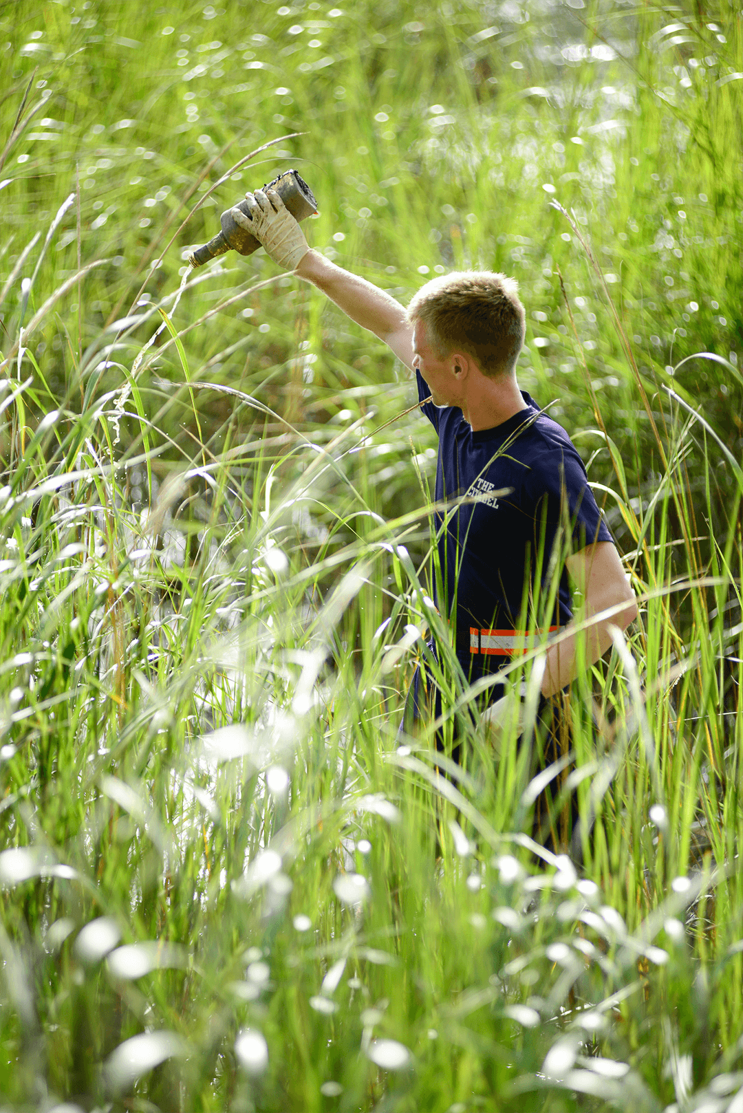 Matthew Miller, '19, participates in an effort to remove trash from the marsh.