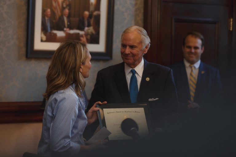 Governor Henry McMaster presents Dr. Dena Garner, The Citadel's director of research, an award of excellence