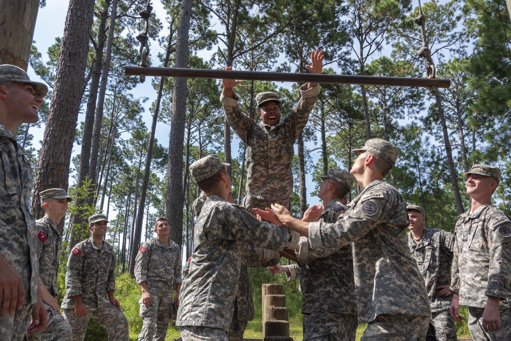 Citadel cadet cadre member jumps through the air in a team-building trust exercise at Parris Island