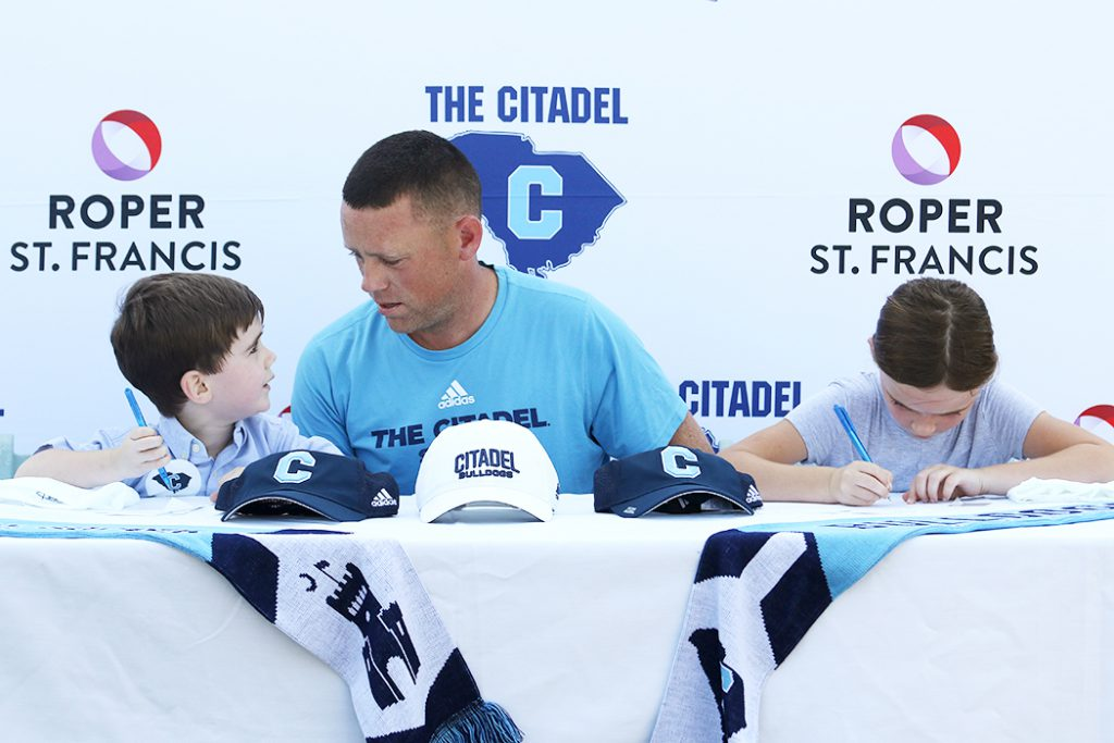 Citadel women's soccer head coach Ciaran Traquair, middle, with Milo, left, and Annie, right
