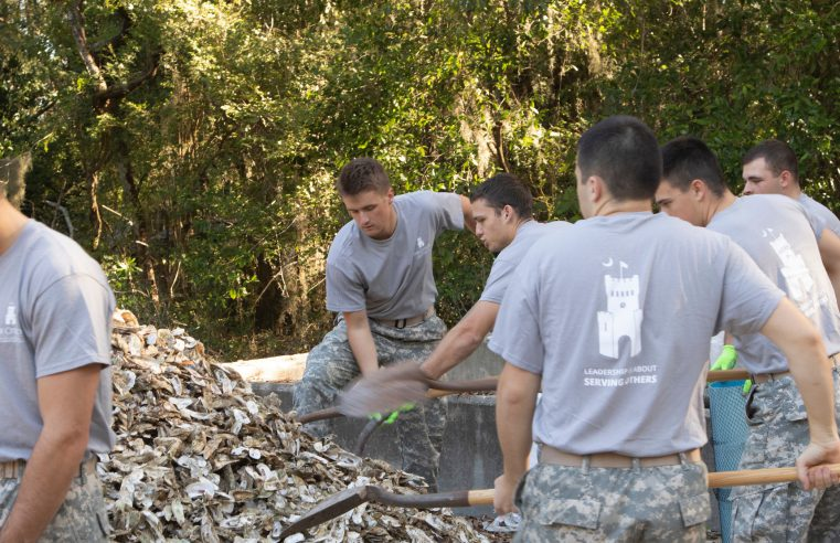 Cadets shoveling oyster shells at U.S. Fish and Wildlife