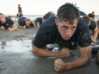 Cadets crawling on the beach in training excercise