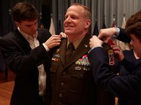 U.S. Army Reserve Maj. Gen. John Phillips smiles as his sons Ryan and Stone pin the two-star insignia to the shoulders of his Army Green Service Uniform during his promotion ceremony held in Alexander Hall, Fort Gordon, Ga. Feb. 9, 2020.