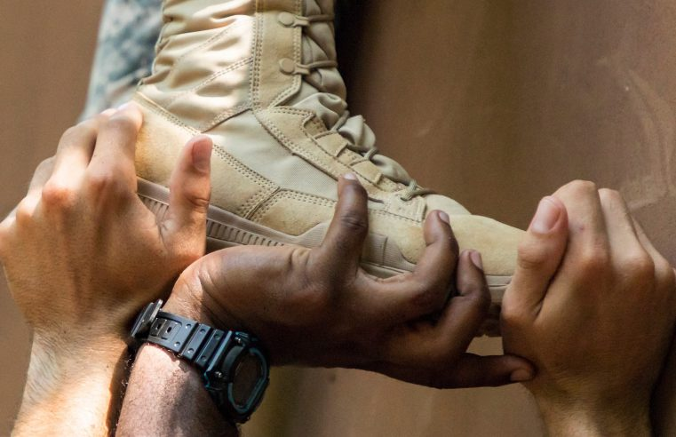 Hands supporting a foot in a military boot