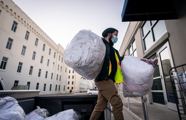 Christopher Jardin, the community liaison and homelessness coordinator for the City of Charleston, unloads laundry from the city's warming centers at the Cadet Laundry at The Citadel in Charleston, South Carolina on Wednesday, December 2, 2020. (Photo by Cameron Pollack / The Citadel)