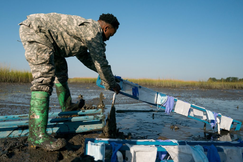 Cadets Jerry Higgins and Douglas Karam, accompanied by Dr. John Weinstein, Biology, deploy an experiment to measure how face masks, rubber gloves and hand wipes decompose in the salt marsh behind Inouye Hall on Thursday, October 14, 2021.  Credit: Cameron Pollack / The Citadel